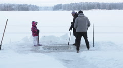 Family finishing to prepare ice-hole, removing big piece of ice under surface Stock Footage
