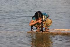 Local girl drinking from water reservoir, Khichan village, India - stock photo