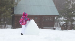 Playful child climbing on huge snowball at rural timber house yard at winter sea Stock Footage