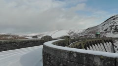 Narrow road leading over Craig Goch dam, covered in snow - stock footage
