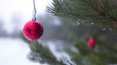 Red Christmas tree ball hanging outdoor on fir tree branch, swinging on wind Stock Footage