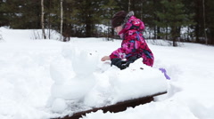 Young girl sitting in snow and making snow sculptures at winter Stock Footage