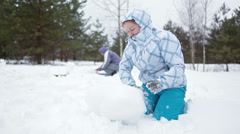 Two Caucasian women making sculptures from snow at winter field Stock Footage