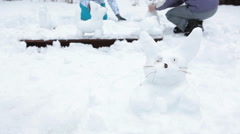 White rabbit from snow on foreground with two people making snowman sculptures - stock footage
