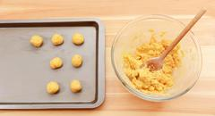 Adding balls of cookie dough to a baking sheet - stock photo