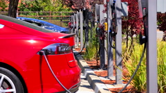 A Tesla electric car charges at a charging station. Stock Footage