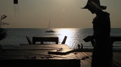 Woman in a cafe by the sea working type on a laptop, freelance, vacation, sunset Stock Footage