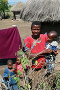 Maasai village, the African family standing near huts. Stock Photos