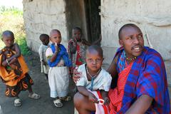 Maasai family at threshold of his house, father and children. Stock Photos