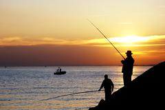 Fisherman silhouettes against sunset Stock Photos