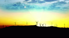 4K LOOP windmill turbines harnessing clean, green, wind energy silhouetted in - stock footage