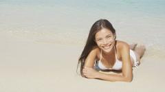 Beach bikini girl lying in sand tropical paradise - Sexy happy woman Stock Footage