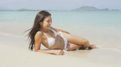 Bikini girl lying on beach sand paradise - sexy happy woman relaxing Stock Footage