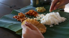 man eats food with hands from banana leaf - stock footage