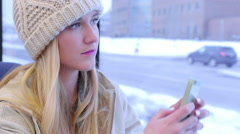 Teen Uses Her Smartphone To Take A Photo Of Snowy Cityscape Outside Train Window Stock Footage