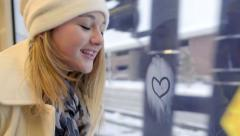 Teen Girl On Train, She Blows On Her Window, Then Draws A Heart - stock footage