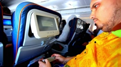 passenger seats on the plane and uses media player. HD. 1920x1080 - stock footage