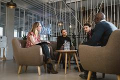 Diverse group of young people having a meeting in lobby Stock Photos