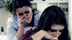Woman crying hugging teenager daughter Stock Footage