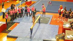 4K collegiate athlete doing back flips on balance beam Stock Footage