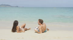 Happy couple relaxing on beach lying sand tanning on summer vacation Stock Footage