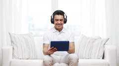 Smiling man with tablet pc and headphones at home Stock Footage