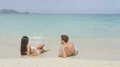 Vacation couple relaxing on beach sand sun tanning and relaxing Stock Footage