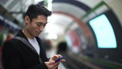 Young asian man types on his phone at a subway station Stock Footage