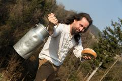 Long-haired grower offering a milk churn and bread Stock Photos