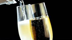 Pouring champagne into flutes with golden bubbles on black background Stock Footage