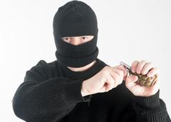 Masked man with grenade - stock photo