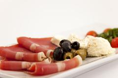 Food plate with ham,olives,cheese,cherry tomatoes and arugula Stock Photos