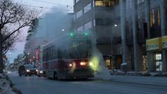Streetcar plows through sewer steam in winter Stock Footage