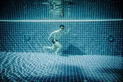 Man runs underwater swimming pool - stock photo