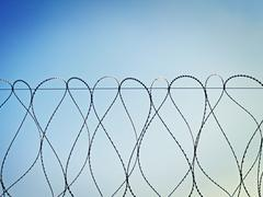 spirals of barbed wire against the sky - stock photo