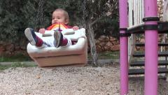 Bored baby on swing Stock Footage