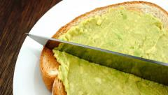 Cutting toast spread with mashed avocado in half - stock footage