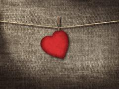 Valentine card heart shaped from old red paperr hanging on a clo - stock photo