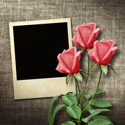 Polaroid-style photo on a linen background  with red roses in vintage style - stock photo