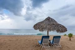 Sunbed and umbrella on a tropical beach Stock Photos