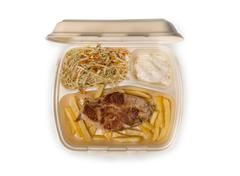 Grilled chicken meat, French fries, and salad in takeout food box Stock Photos
