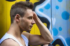 Profile shot of young man next to bright colored graffiti Stock Photos