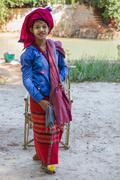 Girl in traditional dress sells textiles crafts at the market of Lake Inle. - stock photo