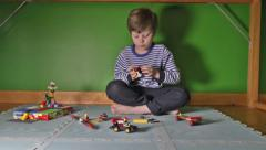 Boy playing with Lego on floor Stock Footage