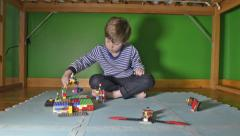Boy playing with Lego in room Stock Footage