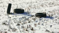 Winter tire rolls on a snowy field Stock Footage