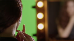 The young woman puts on beautiful earrings. Preparation for the fashion show. Stock Footage
