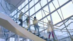 Group Of Teens Run Down Stair Well In Beautiful Glass Building Stock Footage