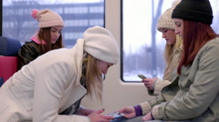 Two Girls Ride Train With Their Friends, They Look At Smartphone And Laugh Stock Footage