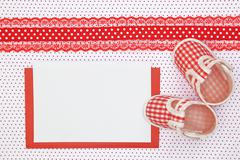 Stock Photo of Baby shoes and blank card on polka dots background